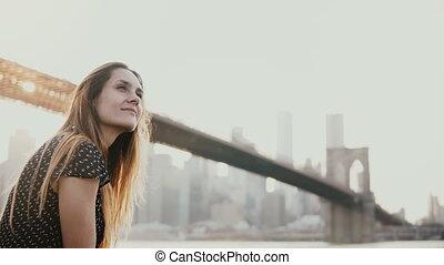 Happy smiling European young woman smiling, enjoying amazing sunset view of New York near Brooklyn Bridge river 4K.