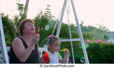Happy smiling Family, grandmother with granddaughter are playing, blowing soap bubbles in the summer outdoor. Stock Footage.