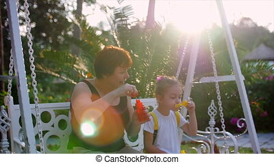 Happy smiling Family, grandmother with granddaughter are playing, blowing soap bubbles in the summer outdoor. Stock Footage. Slow motion.