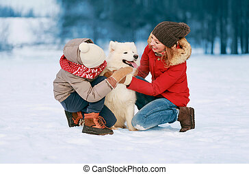 Happy smiling family having fun together in winter day, mother and child walking with white Samoyed dog in snowy park