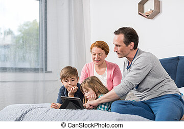 Happy Smiling Family Sitting On Bed Use Tablet Computer, Parents Spending Time With Son And Daughter