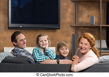 Happy Smiling Family Sitting On Couch In Living Room, Parents Couple With Two Children