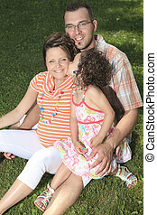 Happy smiling family sitting on the grass