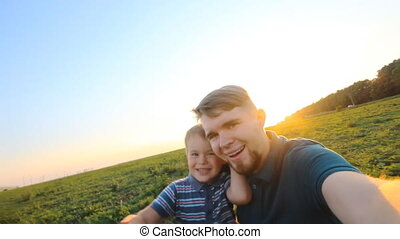 Happy smiling father and son take a self picture slowmotion