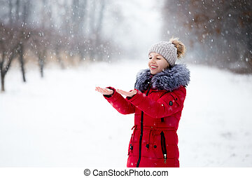 Happy smiling female in red winter jacket catching the snow with her palms, outdoors, in park