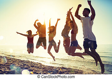 Happy smiling friends jumping at the beach