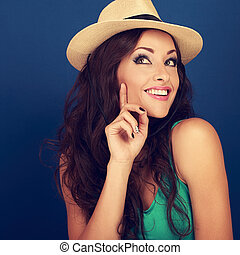Happy smiling fun makeup woman in summer hat thinking and looking on blue background. Closeup bright portrait