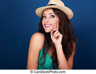 Happy smiling fun makeup woman in summer hat thinking and looking on bright blue background with empty copy space