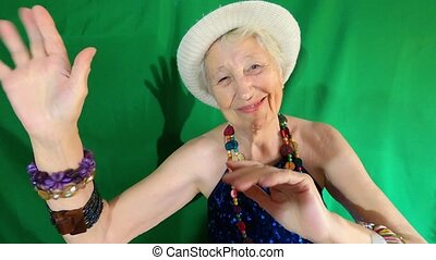 Happy smiling funny senior woman wearing beads dancing at home