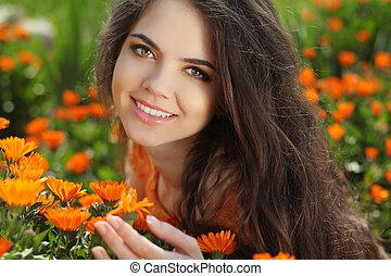 Happy smiling girl. Beautiful Romantic Brunette female Outdoors portrait. Over marigold flowers field. Healthy Long Hair. Enjoyment.