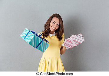 Happy smiling girl in dress holding two gift boxes
