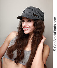 Happy smiling girl in fashion cap. Woman with long curly hair