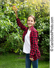 Happy smiling girl in red checkered shirt picking apples at garden