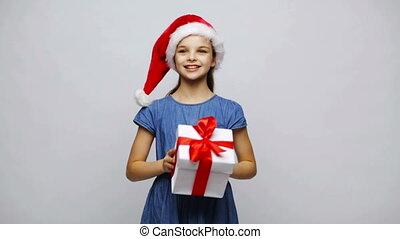 happy smiling girl in santa hat shaking gift box -...