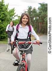 Happy smiling girl in school uniform riding bicycle