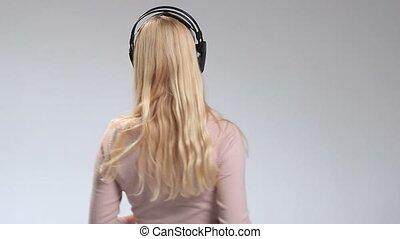 Happy smiling girl listening music in headphones
