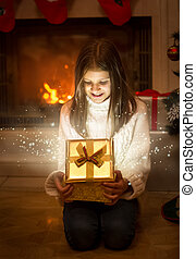 Happy smiling girl opening shiny Christmas gift box. Light and sparkles flying out of box