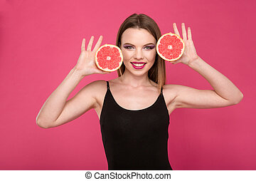 Happy smiling girl posing with two halves of grapefruit