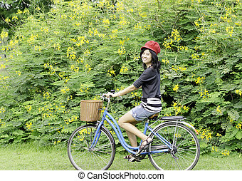 Happy smiling girl riding a bicycle in the park