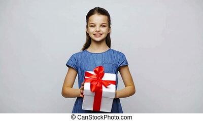 happy smiling girl shaking gift box - childhood, people,...