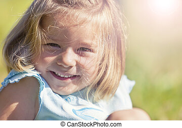 Happy smiling girl sitting in grass