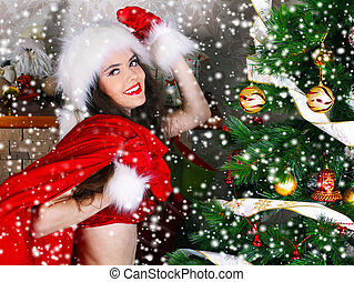 Happy smiling girl with red bag near Christmas decoration