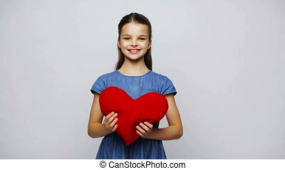 happy smiling girl with red heart shaped pillow