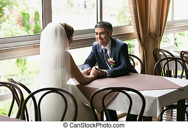 smiling groom and bride sitting at table in restaurant