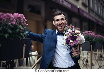 Happy smiling handsome bearded groom in blue suit holding a bouquet with a restaurant in background