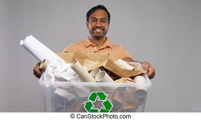 happy smiling indian man sorting paper waste - recycling, ...