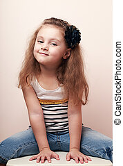 Happy smiling kid girl posing in blue jeans
