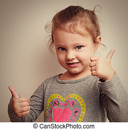 Happy smiling kid with two thumbs up. Closeup vintage portrait