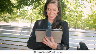 Happy smiling laughing woman wearing business attire working on digital tablet