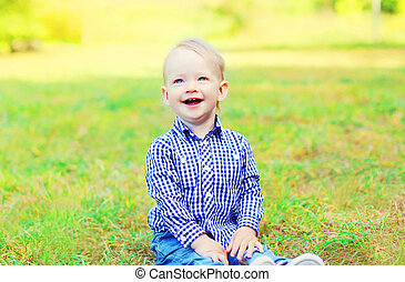 Happy smiling little boy child sitting on grass in sunny day