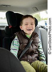 Happy smiling little boy in car safety seat.