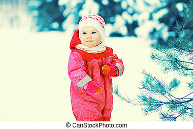 Happy smiling little child walking in winter forest