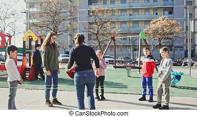 Energetic kids playing and skipping on elastic jumping rope in european yard