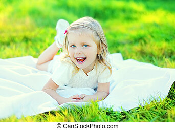 Happy smiling little girl child lying on grass in sunny summer day
