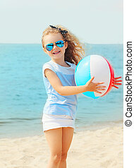 Happy smiling little girl child playing with inflatable water ball on beach near sea summer