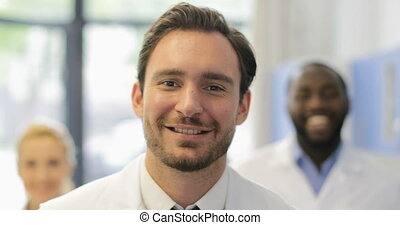 Happy Smiling Male Scientist Walk In Laboratory Over Mix Race Researchers Team In Modern Lab