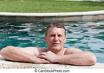 happy smiling man bathes in pool