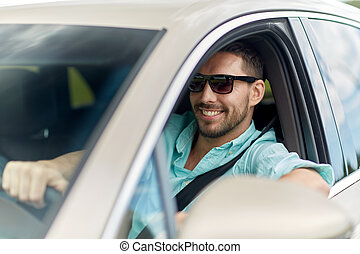 happy smiling man in sunglasses driving car