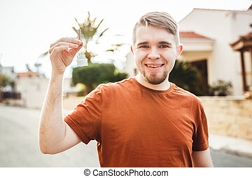 Happy smiling man showing a keys of his new house