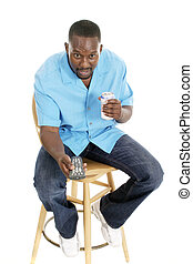 Happy smiling man sitting on a stool holding a remote control and his favorite beverage.