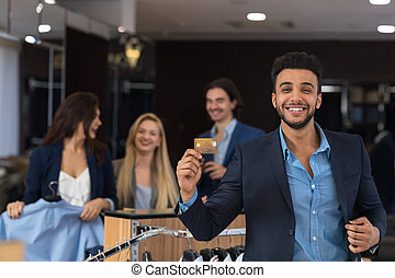 Happy Smiling Man With Credit Card In Clothes Shop