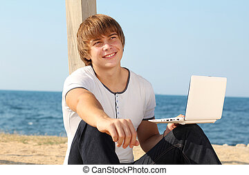 Happy smiling man with laptop on the beach, blue sky