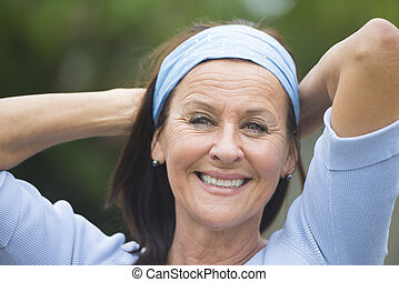 Portrait attractive looking mature woman cheerful, joyful happy smiling outdoor, wearing blue shirt and headband, arms behind neck, blurred background.