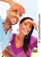Happy smiling middle-aged couple looking at something outdoors