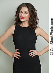 Happy smiling model woman in black dress standing on white background