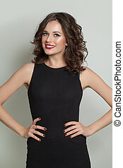 Happy smiling model woman in black dress standing